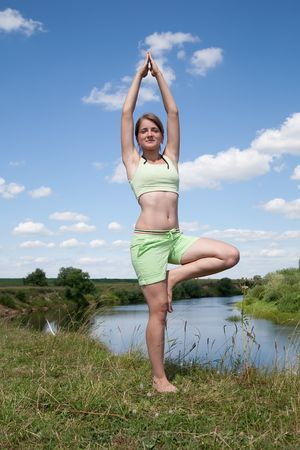 Beautiful young girl practicing yoga  against river Stock Photo - 5543903