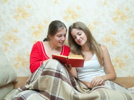 two young girls sitting in the bed and reading a book together  Stock Photo - 5553057