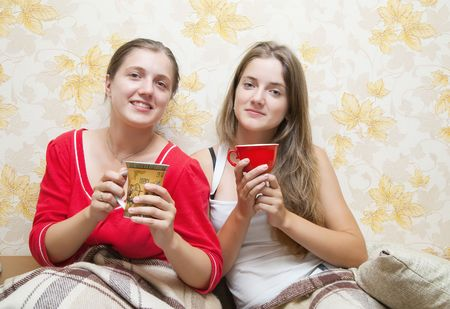 Two smiling girls have tea  in the bed at home photo