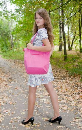 vanity bag: Happy girl in with pink handbag  in autumn park Stock Photo