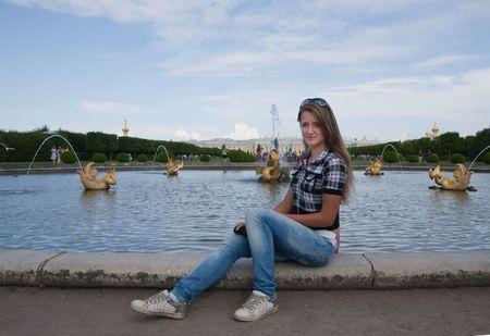 peterhof: Girl sitting near fountain  at Peterhof, Russia