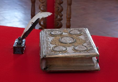 holography: 15st century vintage book and standish on red table
