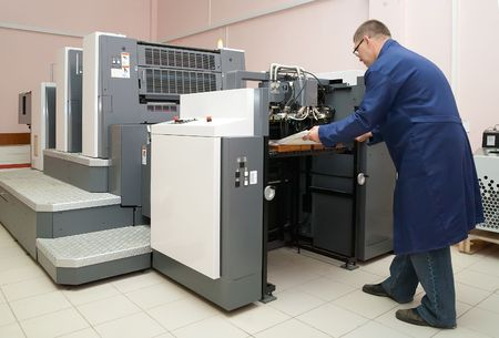 offsetdruck: Drucker arbeitet an seinem neuen Offset-Druckmaschine Lizenzfreie Bilder