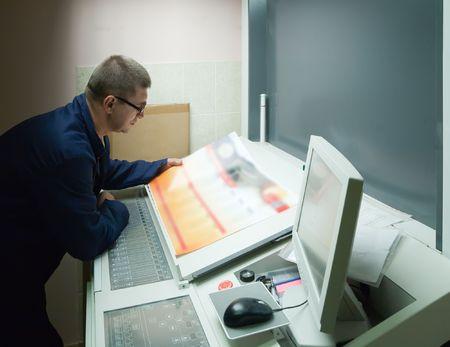 Printer checking a print run at table Stock Photo - 5593147