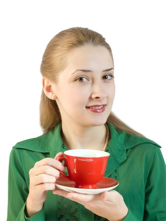 A girl in green blouse drinks tea from a red cup photo