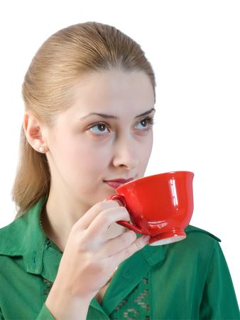 girl in green blouse drinks tea from a red cup.  photo