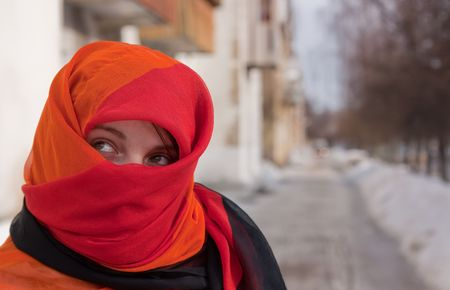 yashmak: young beautiful woman in red purdah against street Stock Photo