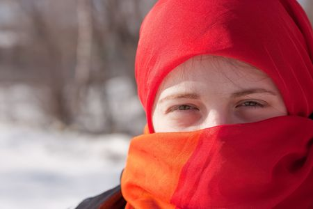 young beautiful woman in red purdah against street photo