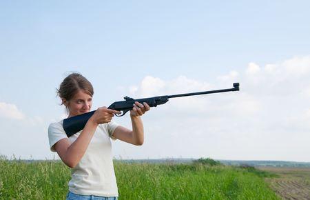 airgun: The woman aiming a pneumatic air rifle