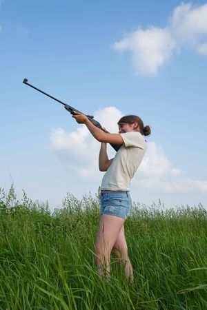 young woman aiming a pneumatic air rifle photo