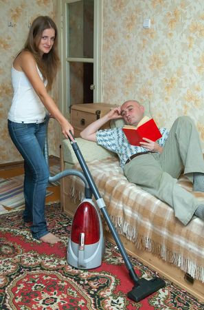 housecleaning: yang womam doing housecleaning and man resting over sofa Stock Photo