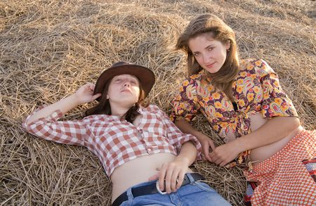 Country girls on fresh hay in summer photo
