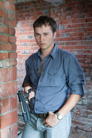 man in blue shirt  standing on brick background holding gun Stock Photo - 5654130