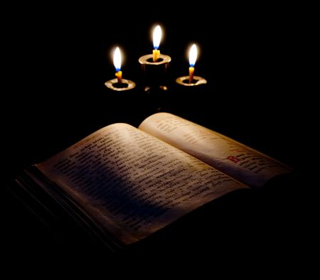 old Psalter and candles in candelabrum. Focus on book photo