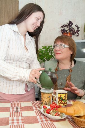 Girl and women drink tea in the kitchen photo