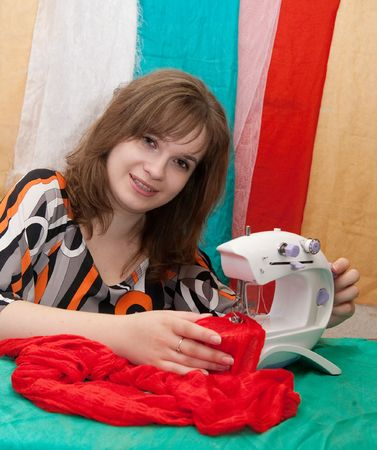 Young woman works at sewing machine in her home photo