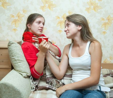 girl gives a cup to unwell girl Stock Photo - 5856340