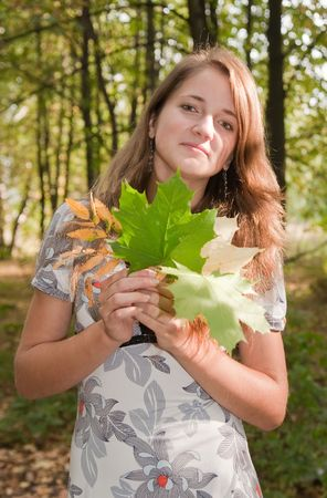 long-haired  girl  with  maple leaf against nature