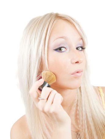 A young woman putting make up on her face with a brush, white background. Stock Photo - 5884984