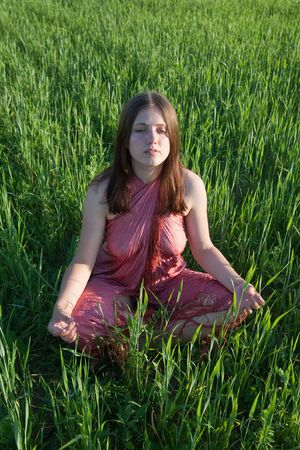Young girl doing yoga against grass during sunset photo