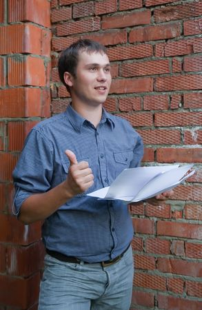 tasker: builder with  thumbs up  against  the brick wall