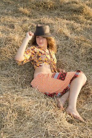 Country girl on fresh hay in summer photo