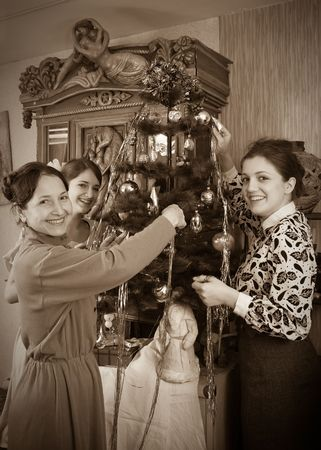 Vintage photo of  Three women decorating Christmas tree at home photo