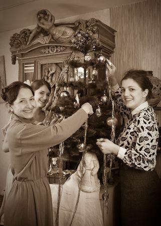 Vintage photo of  Three women decorating Christmas tree at home photo