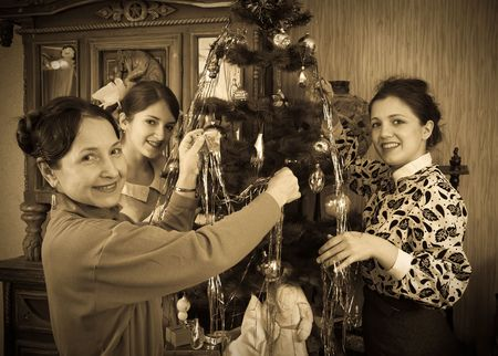 victorian christmas: Retro photo of Teen girls with mother decorating Christmas tree at home Stock Photo
