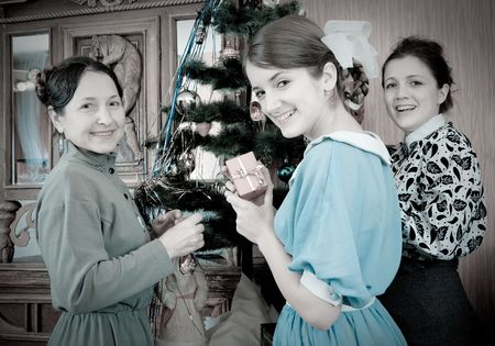 Retro photo of Teen girls with mother decorating Christmas tree at home Stock Photo - 5987702