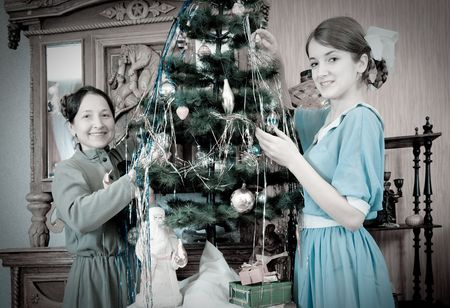 Vintage photo of  daughter with mother decorating Christmas tree at home photo