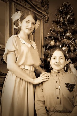 Retro photo of daughter with mother against Christmas tree at home Stock Photo - 6005639
