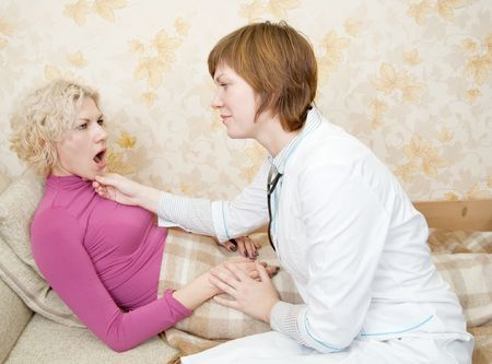 Female doctor loking to suffering girl on bed Stock Photo - 6030691