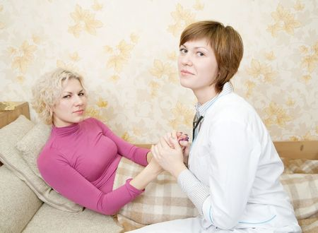 Female doctor loking to suffering girl on bed Stock Photo - 6030680