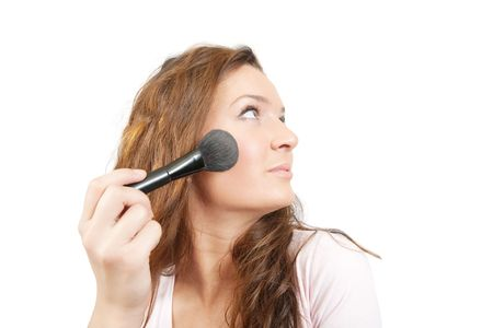 young woman putting make up on her face. Isolated photo