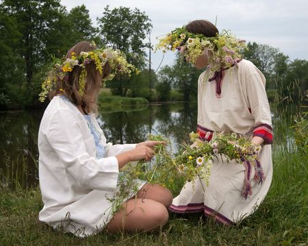 teener: Two girls traditional clothes is twine a wreath of flowers against lake Stock Photo