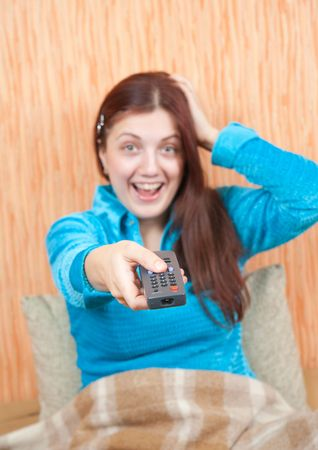 clicker: Young woman smiling with TV remote control. Focus on clicker