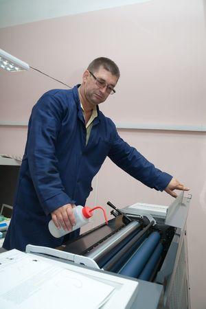 ofset: Printer working at his modern offset machine