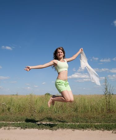 Jumping long-haired teen girl against blue sky photo