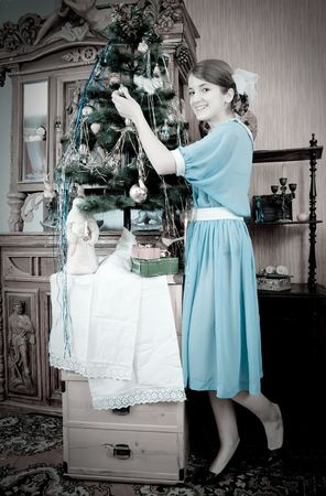 Retro photo of Teen girl decorating Christmas tree at home photo