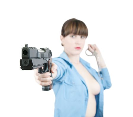 Topless woman in uniform with gun and manacles over white, Focus on gau only photo