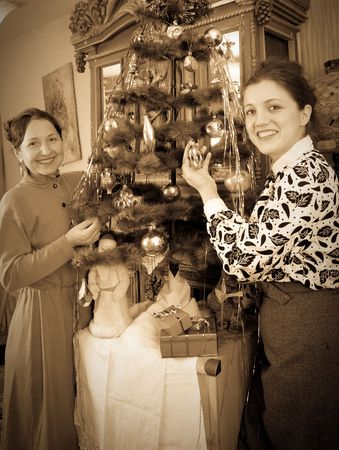 Retro photo of Two women decorating Christmas tree at home photo