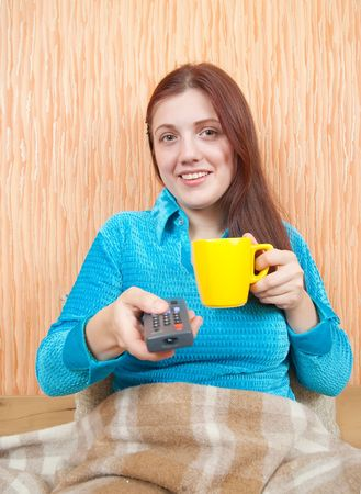 Young woman smiling with TV remote control and cup of tea photo