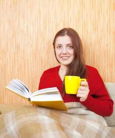 young woman sitting on the sofa reading and drinking coffee  photo