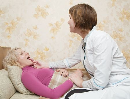 Female doctor loking to suffering girl on bed Stock Photo - 6123217