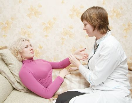 stupes: Female doctor loking to suffering girl on bed Stock Photo