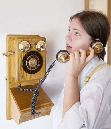 Portrait of girl is speaking by retro wooden phone photo