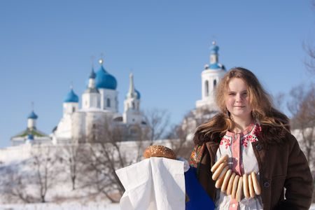maslenitsa: Smiling girl in russian traditional  clothes  with loaf against  Russian landscape