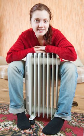 woolley: young smiling girl is sitting by a oil heater  Stock Photo