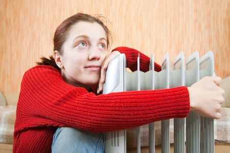young smiling girl is sitting near oil heater Stock Photo - 6190428